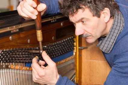 Piano-Tuner-working-on-upright-piano